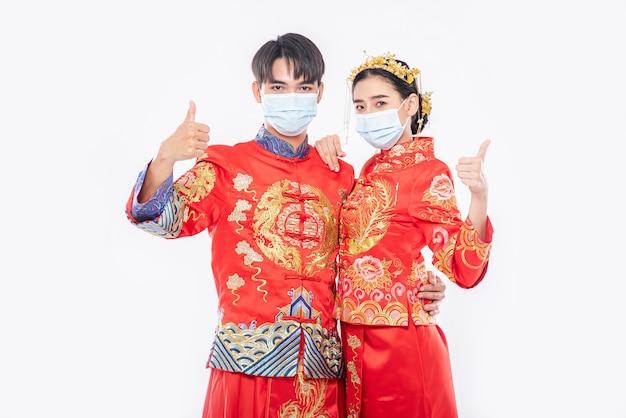 Man en vrouw dragen cheongsam-pak en masker. duim omhoog voor het evenement zal plaatsvinden op chinees nieuwjaar