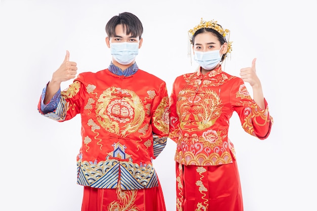 Man en vrouw dragen cheongsampak en masker thumbs up to the world can be produce vaccins to protect covid-19
