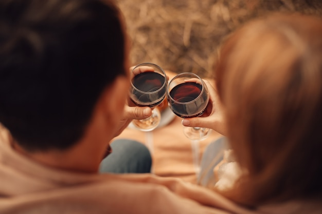 Man en vrouw drinken van rode wijn, close-up handen met glazen.