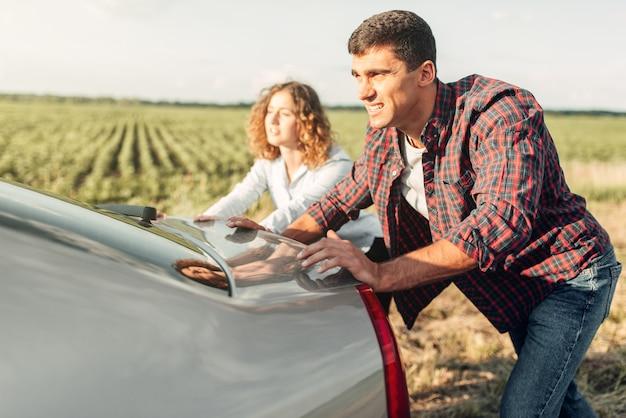 Man en vrouw duwen een kapotte auto, achteraanzicht