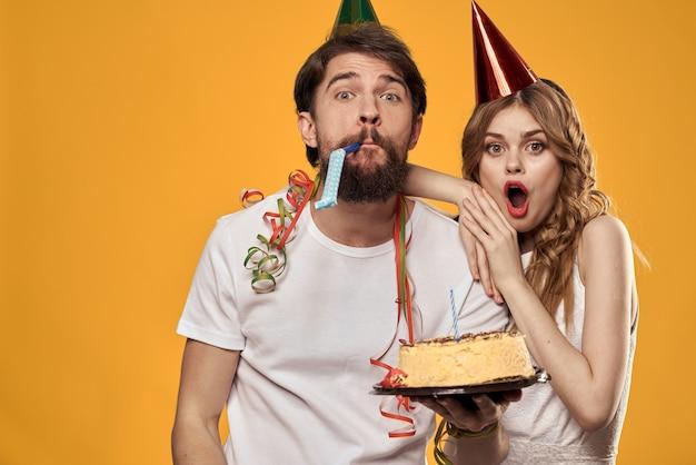 Man en vrouw feestelijke verjaardagstaart gele achtergrond en caps op de headv