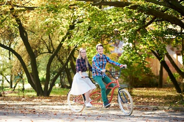 Man en vrouw fietsen samen tandem dubbele fiets