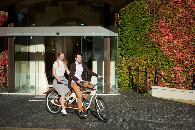 Man en vrouw fietsen tandem fiets