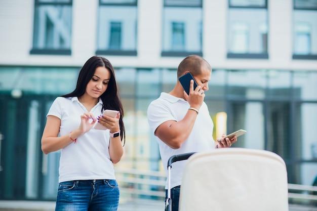 Man en vrouw gebruiken telefoons. kind in rolstoel, concept drukke ouders