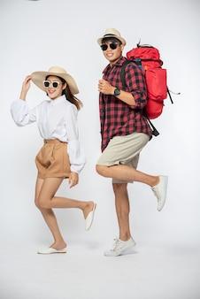 Man en vrouw gekleed met een bril om met koffers te reizen