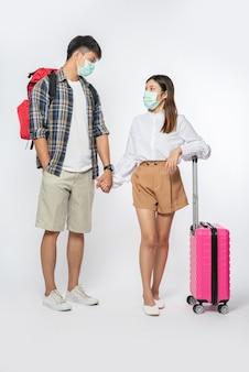 Man en vrouw gekleed om te reizen, met maskers en bagage