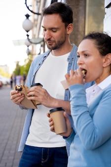Man en vrouw genieten van afhaalmaaltijden op straat