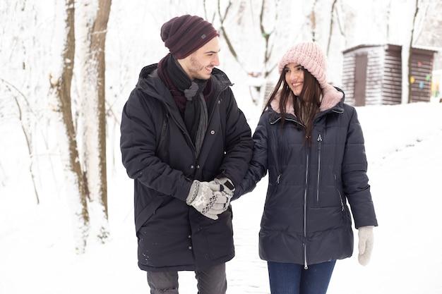 Man en vrouw genieten van winter en sneeuw in park