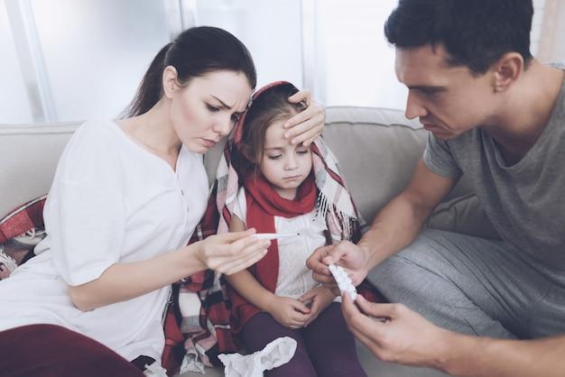 Man en vrouw geven om een dochter met verkoudheid.