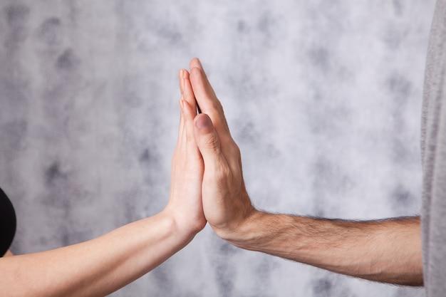 Man en vrouw geven vijf op grijs
