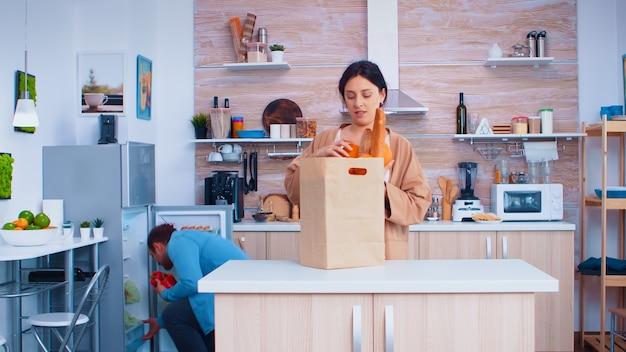 Man en vrouw halen groenten uit een papieren zak. vriend arriveert uit de supermarkt. vrolijke gelukkige familie gezonde levensstijl, verse groenten en boodschappen. supermarkt producten shoppi