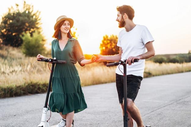 Man en vrouw hand in hand op elektrische scooters