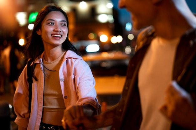 Man en vrouw hand in hand 's nachts in de stadslichten