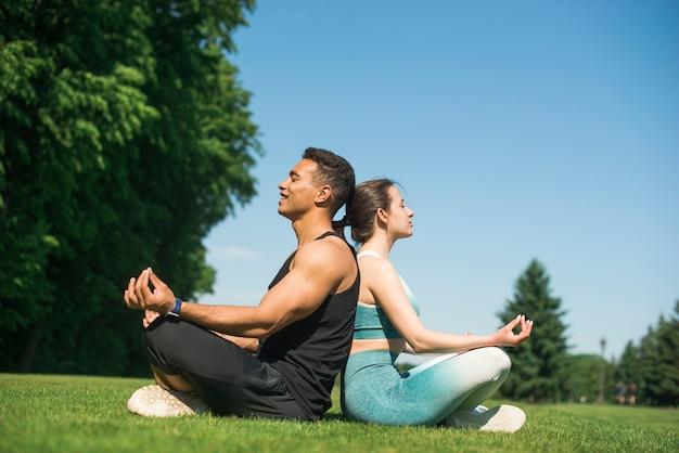 Man en vrouw het beoefenen van yoga buiten