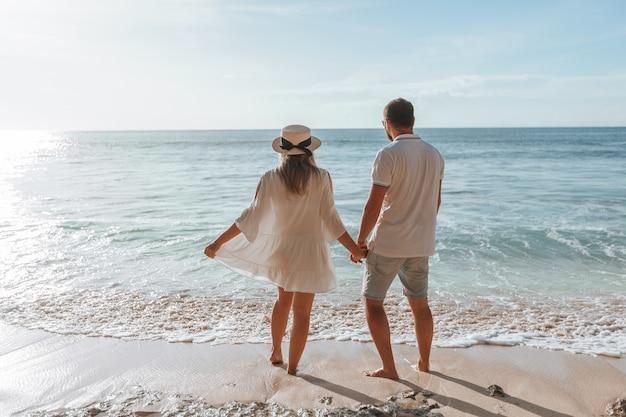 Man en vrouw houden elkaars hand vast en kijken naar de zonsondergang op het strand