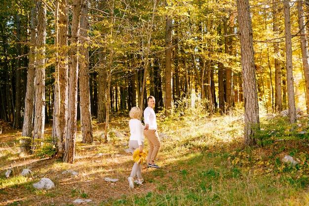 Man en vrouw houden elkaars hand vast in het herfstbos vrouw heeft een boeket gele bladeren