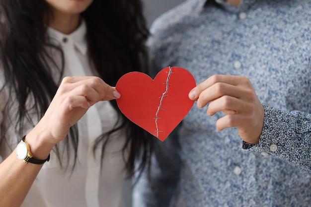 Man en vrouw houden gelijmd hart vast. familie relatie problemen concept