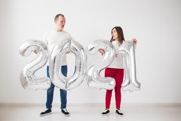 Man en vrouw houden zilverkleurige cijfers vast