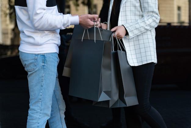 Man en vrouw houden zwarte boodschappentassen vast. meisje en jongen ontmoeten elkaar na het winkelen. bespotten. zwarte vrijdag-concept.
