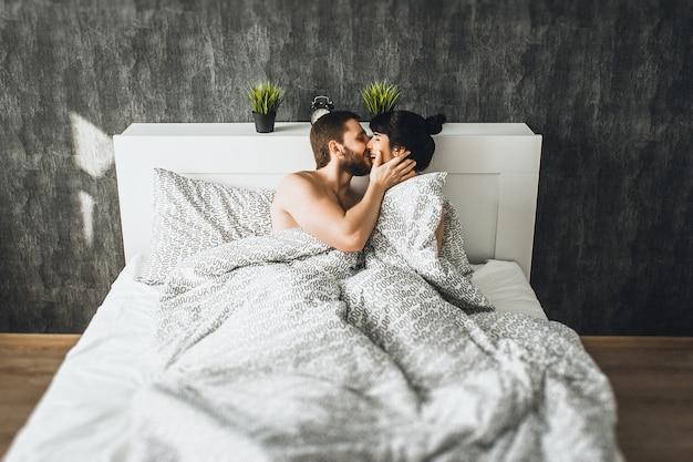 Man en vrouw in bed. jongen en meisje hebben seks. verliefde paar in bed. huwelijksnacht. pasgetrouwden kussen. de liefde bedrijven. liefhebbers in bed. de relatie tussen een man en een vrouw. seks tussen een man en een vrouw
