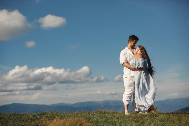 Man en vrouw in de bergen. jong paar verliefd bij zonsondergang. vrouw in een blauwe jurk. peopel staande op een hemelachtergrond.