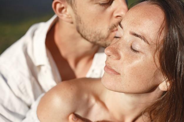 Man en vrouw in de bergen. jong paar verliefd bij zonsondergang. vrouw in een blauwe jurk.