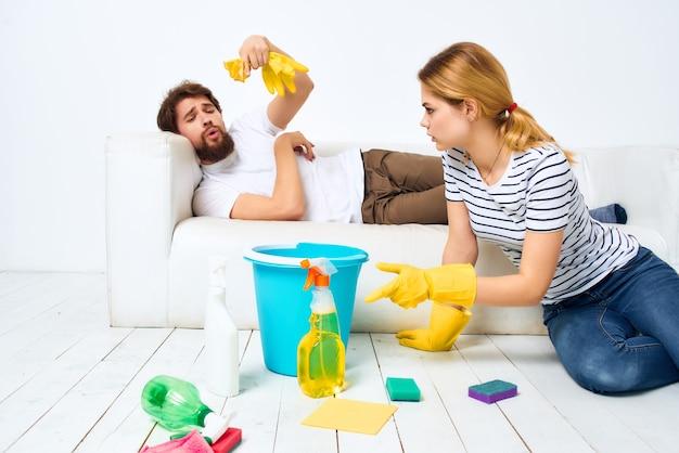 Man en vrouw in de buurt van de bank die de lichte achtergrond van het appartement schoonmaakt