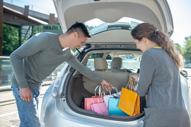 Man en vrouw in de buurt van de open kofferbak van de auto