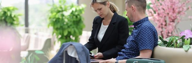 Man en vrouw in de lobby van het hotel kijken naar informatie op laptop