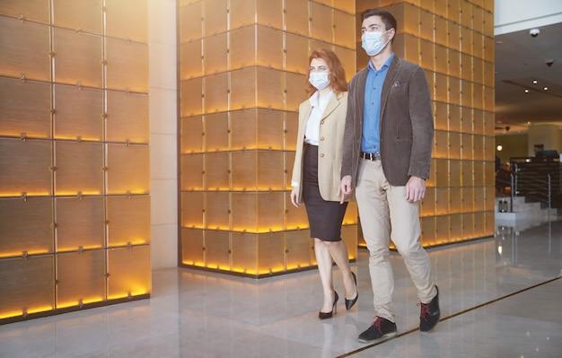 Man en vrouw in elegante kleding lopen door de hal met medische maskers op hun gezicht terwijl ze de sanitaire regels volgen