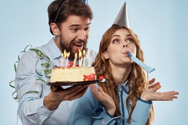 Man en vrouw in feestmutsen met verjaardagstaart op een blauwe achtergrond