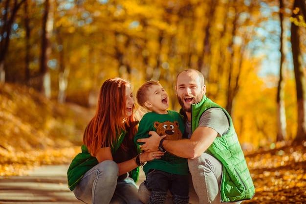 Man en vrouw in groene jasjes lopen met hun zoontje