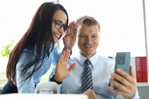 Man en vrouw in het kantoor begroeten gesprekspartner voor een online oproep op smartphone