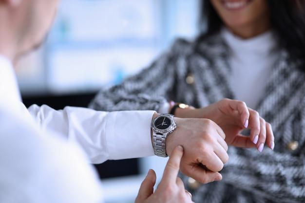 Man en vrouw in kantoor controleren tijd op polshorloge