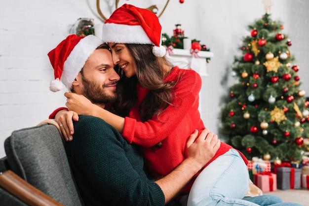 Man en vrouw in kerstmishoeden die op bank omhelzen