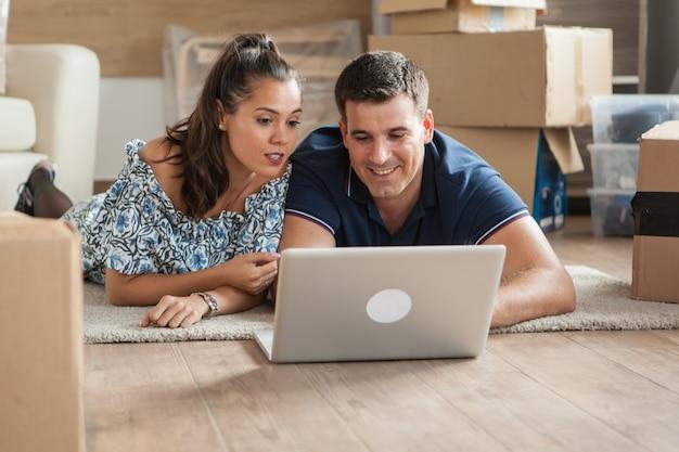 Man en vrouw in nieuw appartement op de grond liggen en online winkelen op een computer voor nieuwe meubels