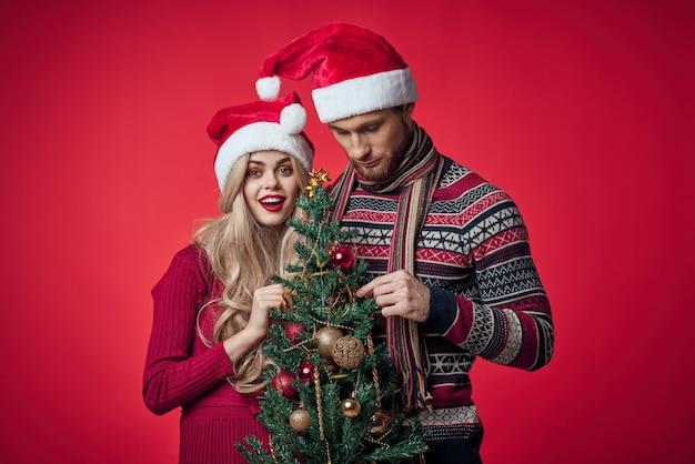 Man en vrouw in nieuwe jaarkleren samen vakantiegiften rode achtergrond