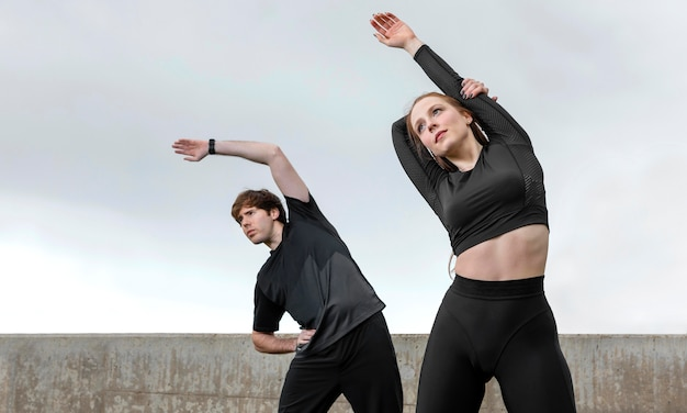 Man en vrouw in sportkleding buiten oefenen