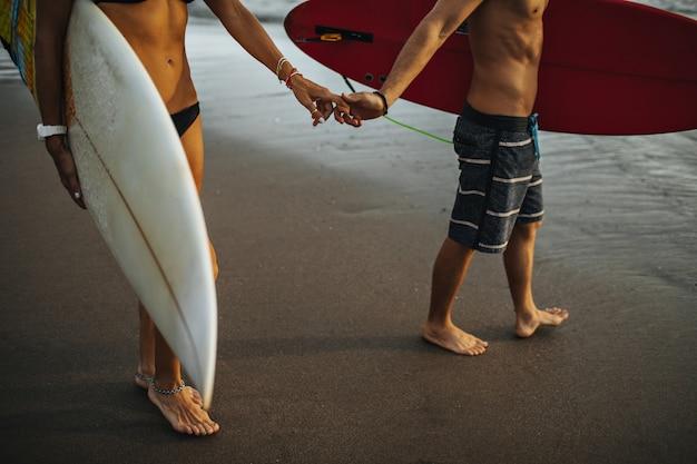Man en vrouw in strandoutfits die op nat zand lopen en surfplanken dragen