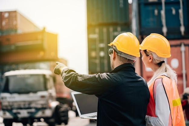 Man en vrouw in veiligheid jumpsuit werkkleding met gele veiligheidshelm
