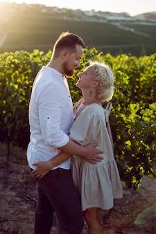 Man en vrouw in witte kleren staan bij zonsondergang in een druivenveld