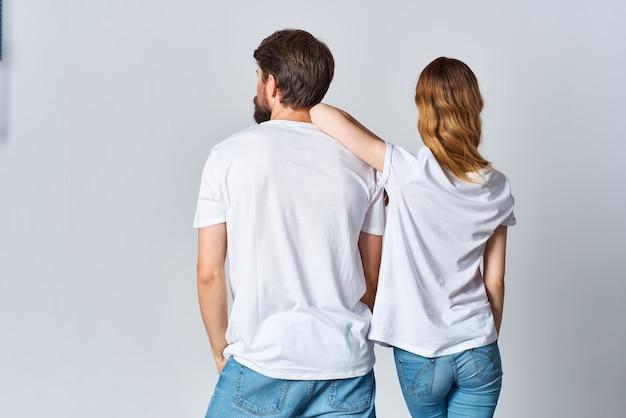 Man en vrouw in witte t-shirts en jeans ontwerpen casual kledingmodel