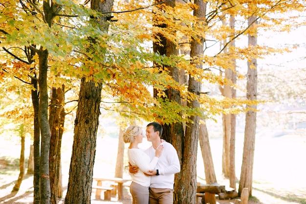 Man en vrouw in witte truien knuffelen op een scène van gele en rode bladeren in de herfst