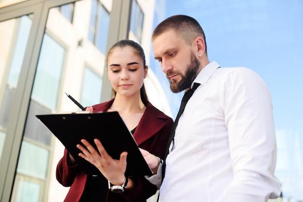 Man en vrouw in zakelijke kleding ondertekenen documenten of een contract
