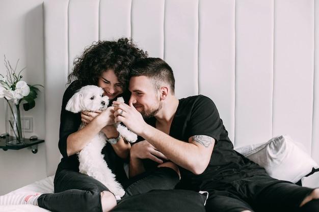 Man en vrouw in zwart spel met kleine witte hond op bed