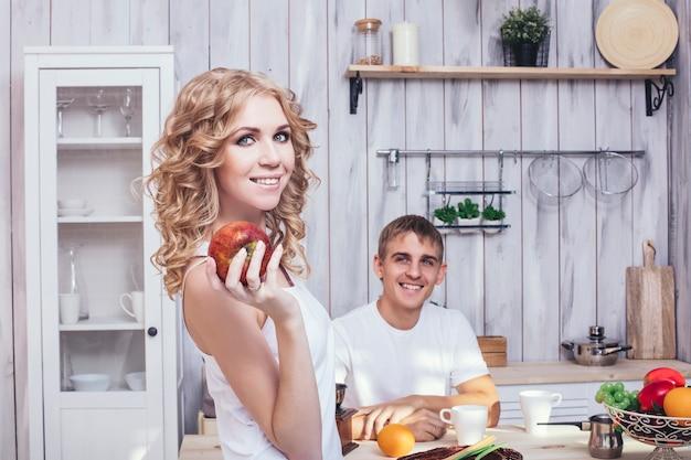 Man en vrouw jong en mooi paar in de keuken thuis koken en hebben samen ontbijt, elkaar helpen