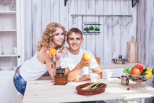 Man en vrouw jong en mooi paar in de keuken thuis koken en samen ontbijten