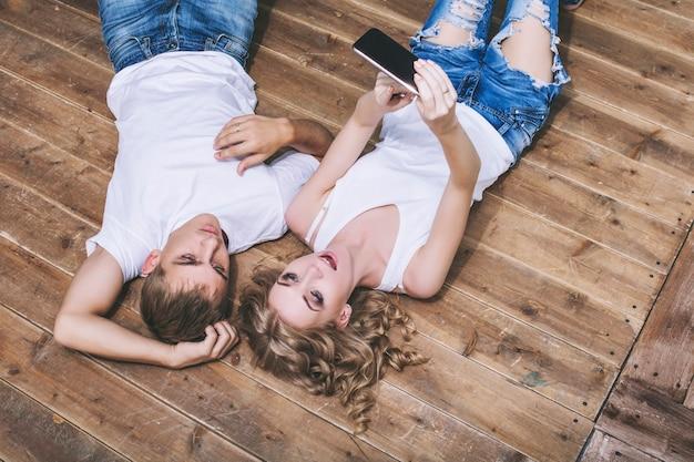 Man en vrouw jong en mooi paar in witte overhemden die selfies op de gelukkige houten vloer nemen