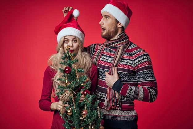 Man en vrouw kerstboom speelgoed leuke vakantie rode achtergrond