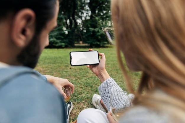 Man en vrouw kijken naar een telefoon terwijl ze buiten een picknick hebben